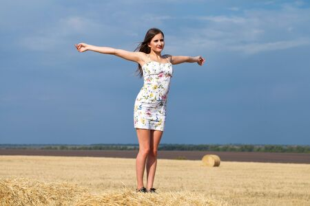 Young beautiful brunette woman in white dress in the hayloft Standard-Bild