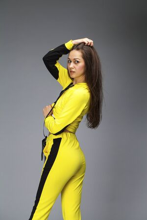 Back view woman. Portrait of a young beautiful brunette woman in yellow tracksuit, isolated on gray background