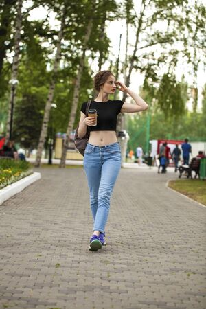 Young beautiful brunette woman in blue jeans and t-shirt walking in summer park