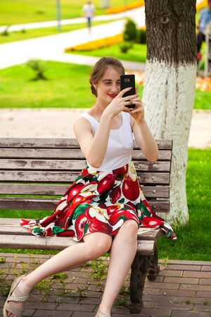 Calling by phone. Young beautiful girl in summer dress sitting on a park bench 写真素材
