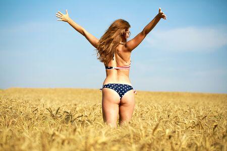 Back view, beautiful blonde woman in sexy American flag bikini in a wheat field Stock Photo - 127615721