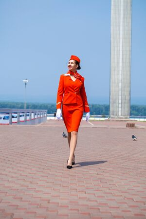 RUSSIA, SAMARA: 26 JULE 2019. Beautiful stewardess dressed in official red uniform of Aeroflot Airlines, Summer Samara outdoors Banque d'images