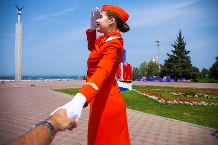 Follow Me, Beautiful stewardess dressed in official red uniform of Airlines, Summer park outdoors Foto de archivo