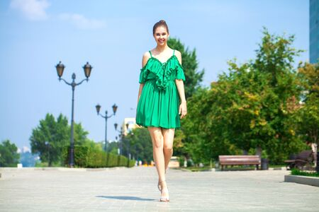 Portrait in full growth, young beautiful brunette woman in a green dress walking on the street, summer embankment outdoors