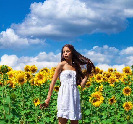 Retrato de una joven hermosa en un campo de girasoles de cerca