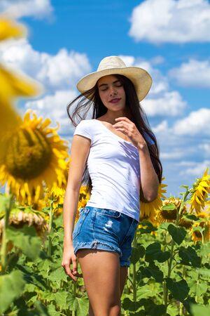 Bouchent le portrait d'une belle jeune fille dans un champ de tournesols Banque d'images