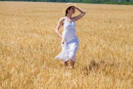 Full body, young brunette woman in white dress walking in a wheat field