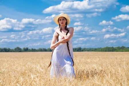 Full body, young brunette girl in white dress and straw hat walking in a wheat field 版權商用圖片