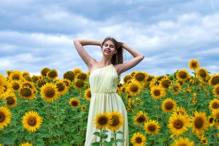 Close up portrait of a young beautiful girl in a field of sunflowers