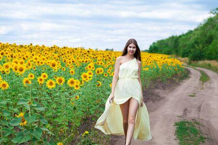 Bouchent le portrait d'une belle jeune fille dans un champ de tournesols