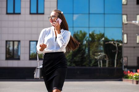 Business woman walking in summer street. Beautiful young brunette girl in black skirt and white blouse calling by phone Stock Photo