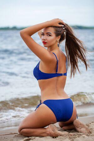 Beautiful brunette woman in blue bikini posing sitting on the sand at the beach Imagens