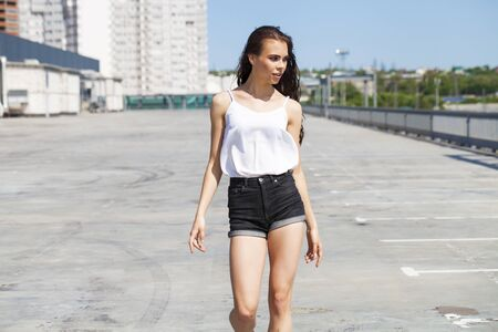 Portrait of a pretty young brunette model in white summer blouse and jeans walking on summer street, outdoors