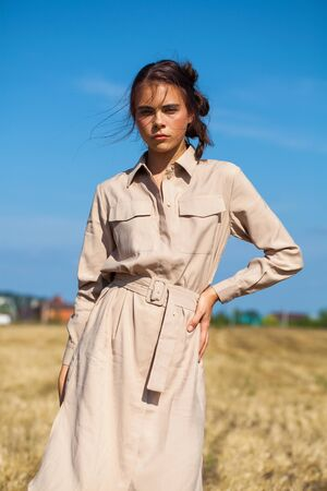 Close up portrait young beautiful brunette girl in a beige dress posing against the background of a mowed wheat field