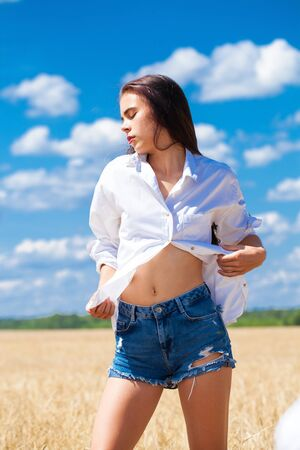 Portrait of a young brunette woman in white shirt and blue jeans shorts on a background of golden wheat field, summer outdoors
