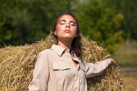 Young beautiful brunette woman in a beige dress posing on a background of haystacks in a cut field Stok Fotoğraf