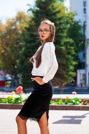 Close up portrait of a young brunette woman in a black skirt and white blouse posing on a street background
