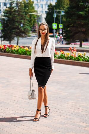 Full-length portrait of a young beautiful woman in a black skirt and white blouse posing on a street background Banco de Imagens