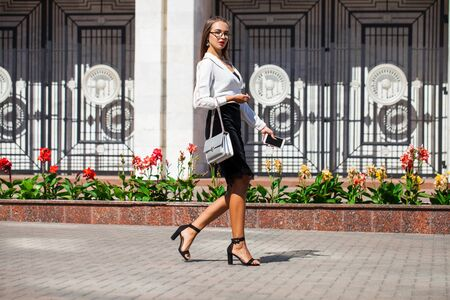 Business woman walking in summer street. Beautiful young brunette girl in black skirt and white blouse