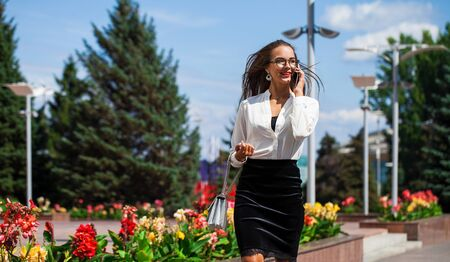 Business woman walking in summer street. Beautiful young brunette girl in black skirt and white blouse calling by phone Stock fotó
