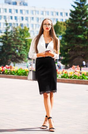 Full-length portrait of a young beautiful woman in a black skirt and white blouse posing on a street background 스톡 콘텐츠