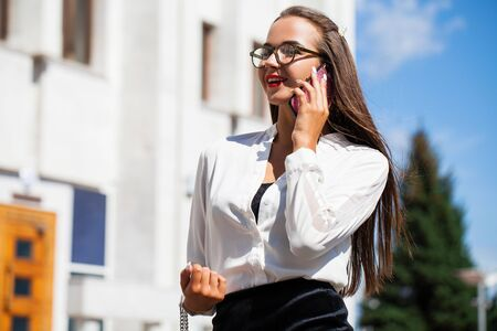 Business woman walking in summer street. Beautiful young brunette girl in black skirt and white blouse calling by phone 스톡 콘텐츠