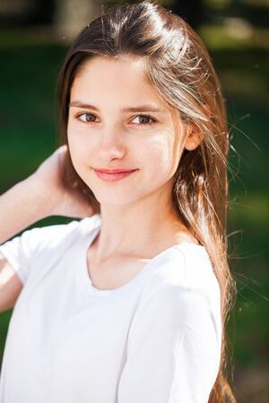 Portrait of a young beautiful brunette girl in white t-shirt on a background of a summer park 스톡 콘텐츠