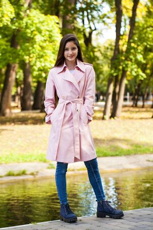 Portrait of a young beautiful brunette girl in pink coat on a background of autumn park 스톡 콘텐츠