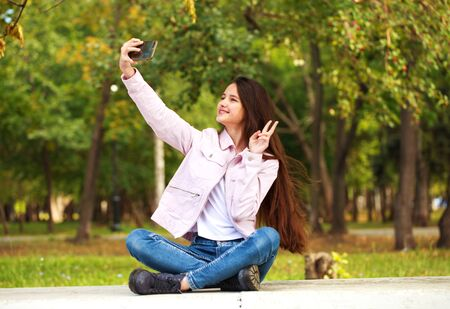 Young beautiful girl photographs herself on a cell phone while sitting in an autumn park. 스톡 콘텐츠