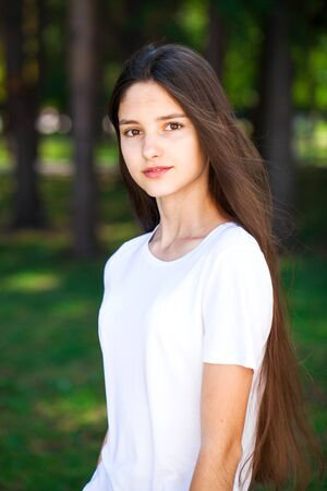 Portrait of a young beautiful brunette girl in white t-shirt on a background of a summer park Stok Fotoğraf