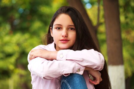 Portrait of a young beautiful brunette girl in pink jacket on a background of autumn park Foto de archivo - 129376960