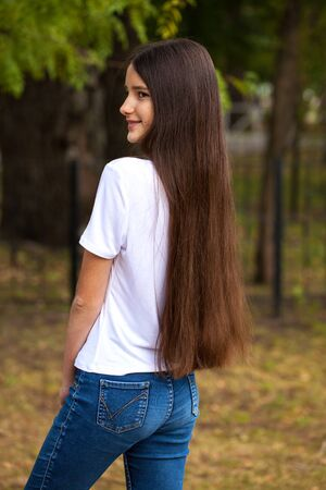Portrait of a young beautiful brunette girl in white t-shirt on a background of a summer park Foto de archivo - 129376963