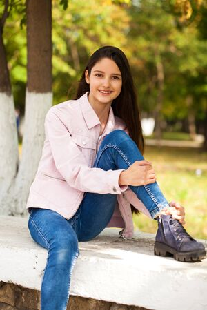 Portrait of a young beautiful brunette girl in pink jacket on a background of autumn park Foto de archivo - 129376959
