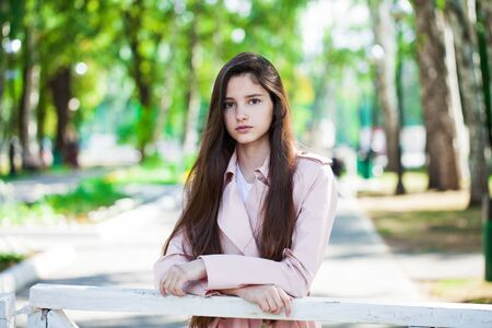 Portrait of a young beautiful brunette girl in pink coat on a background of autumn park Stok Fotoğraf