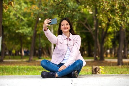 Young beautiful girl photographs herself on a cell phone while sitting in an autumn park. Banco de Imagens