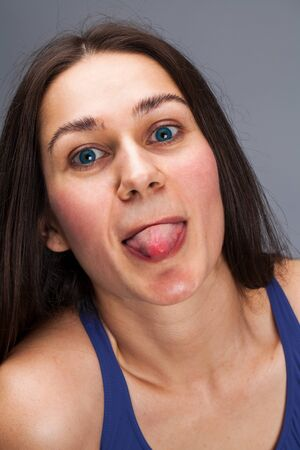 Closeup on mouth of females face, showing tongue. Beautiful brunette woman on  grey studio isolated Фото со стока - 130043633