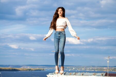 Pretty stylish brunette girl in blue jeans and white blouse jumping on blue sky background