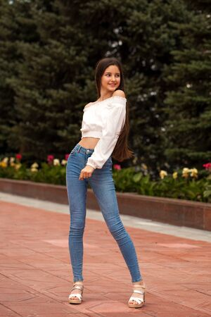 Pretty stylish brunette girl in blue jeans and white blouse posing in summer park background