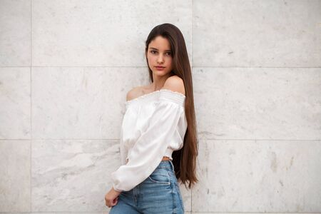 Closeup portrait of a young beautiful girl on a background of a white marble wall