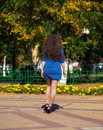 Portrait in full growth, young beautiful brunette woman in a blue dress walking on the street, summer embankment outdoors