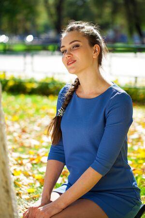 Close up portrait young beautiful brunette woman in blue dress in autumn park