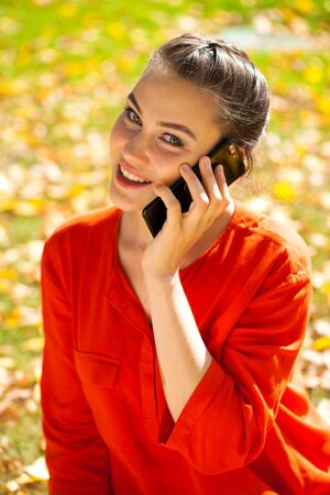 Calling by phone. Portrait close up of young beautiful brunette woman, summer park outdoors