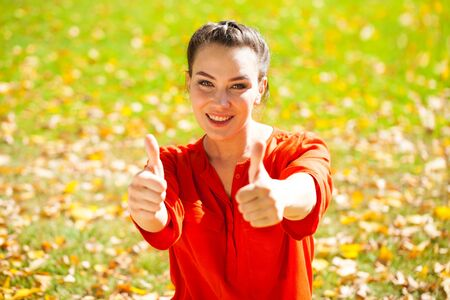 Portrait close up of young beautiful brunette woman in red shirt, autumn park outdoors