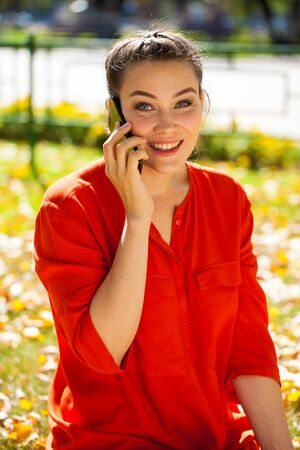 Calling by phone. Portrait close up of young beautiful brunette woman, autumn park outdoors