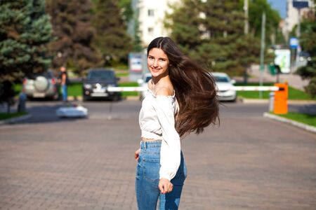 Portrait of young beautiful brunette woman in jeans and white blouse walking in summer street