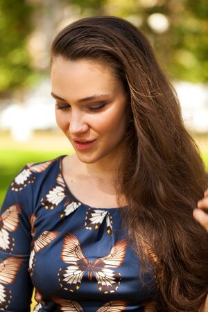 Portrait close up of young beautiful brunette woman in butterfly blue dress, summer park outdoors