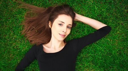 Top view portrait of a young beautiful woman in black dress lies on a green lawn in a park Imagens