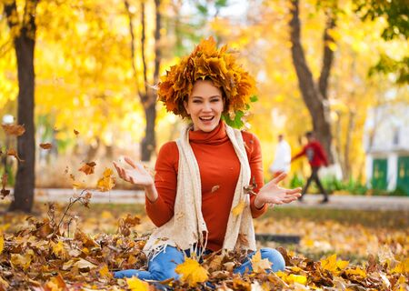 Full body portrait of a young beautiful woman with a wreath of maple leaves posing in autumn park