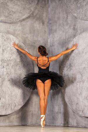 Full body back view portrait. Young ballerina in a black dancing suit is posing in dark studio