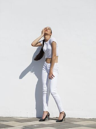 Model tests. Young beautiful brunette girl posing against a white wall in bright sunny weather Stock fotó